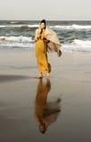 Woman walking along the beach Stock Photography