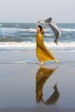 Woman walking along the beach Stock Image