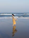 Woman walking along the beach Royalty Free Stock Image