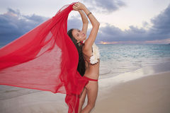 Woman walking along a beach at sunrise. Beautiful young woman walking along Lanikai Beach at sunrise with a red chiffon scarf in hawaii Royalty Free Stock Photography