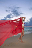 Woman walking along a beach at sunrise. Beautiful young woman walking along Lanikai Beach at sunrise with a red chiffon scarf in hawaii Stock Image