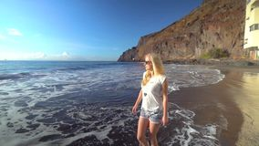Woman walking along the beach stock footage