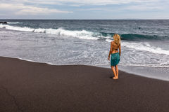 Woman walking along black sand beach in Padangbai, Bali Island, Indonesia Royalty Free Stock Images