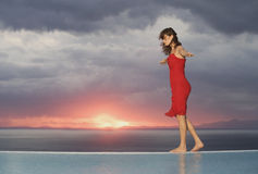 A woman walking along the edge of a pool at sunset Stock Photo