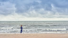Woman walking along the edge of the surf on a beach. In a blue denim outfit looking out to sea on a cold cloudy day with copy space stock photography