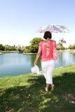 Woman walking along a lake Stock Photography