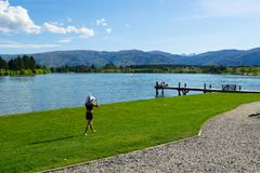 Woman walking along lake edge and group young people sitting together on end of jetty. CROMWELL NEW ZEALAND - OCTOBER 21 2019; Lake Dunstan scene with young royalty free stock image