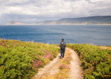 Woman walking along a path on the coast Stock Images