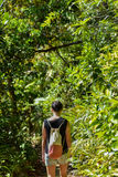 Woman walking along a path through jungle Royalty Free Stock Images