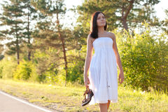 Woman walking along the road Royalty Free Stock Image
