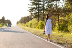 Woman walking along the road Royalty Free Stock Images