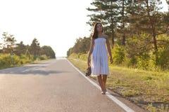 Woman walking along the road Stock Photos