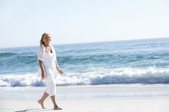 Woman Walking along Sandy Beach Stock Images