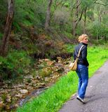 Woman Walking along Stream Royalty Free Stock Images