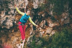 Highline in the mountains. A woman is walking along a stretched sling. Highline in the mountains. Woman catches balance. Performance of a tightrope walker in royalty free stock images
