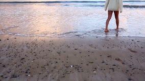 Woman walking along the water at sunset and paddling