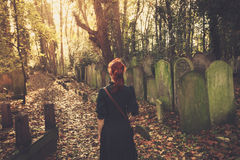Woman walking amongst tombstones Stock Photos