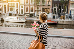 Woman walking in Amsterdam city. Lifestyle portrait of a woman walking with bouquet of pink tulips near the water channel in Amsterdam city Royalty Free Stock Photo
