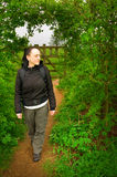 Woman walking through arch in hedge in countryside Stock Image