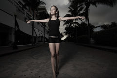 Woman walking with arms extended. Beautiful young woman walking and extending her arms outward Stock Photo