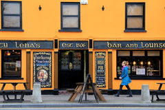 Woman walking by Aunty Lena's, popular bar and lounge,Village Of Adare,Ireland,October,2014. Bright and colorful front entrance of famous Aunty Lena's bar and Stock Photography