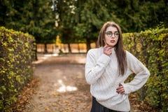 Woman walking in autumn garden near garden Stock Photos