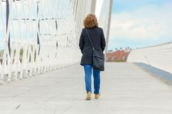 Woman walking away across a pedestrian bridge. Woman wearing jeans and a warm coat with a large bag over her shoulder walking away across a pedestrian bridge royalty free stock images