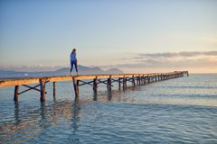 Woman walking away from the camera. Along a wooden pier or boardwalk at sunset over a calm ocean with colorful orange glow in the sky stock photos