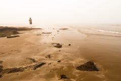 Woman Walking Away. Into fog at the sea shore Royalty Free Stock Photos