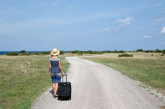 Woman walking away at a gravel road Stock Photo