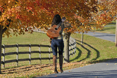 Woman Walking Away with Guitar in the Fall royalty free stock photography