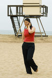 Woman walking away from life guard tower, smiling Royalty Free Stock Image