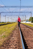 Woman walking away railroad track Royalty Free Stock Photo