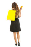 Woman walking away with a shopping bag and a credit card in her Royalty Free Stock Photography