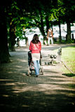 Woman walking with baby carriage Stock Photos