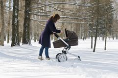 Woman walking with baby carriage. Young woman walking with baby carriage in park Royalty Free Stock Images