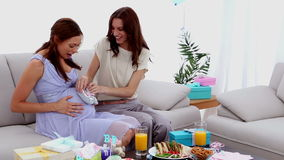Woman walking baby shoes across pregnant friends belly stock footage