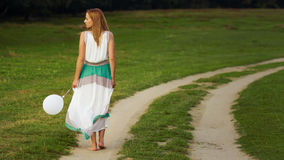Woman walking with balloon in hand Royalty Free Stock Image