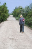 Woman Walking Barefoot. Back view of a woman walking alone on a dirt road, with a pair of red shoes tied together by the laces and slung over her shoulder royalty free stock photography