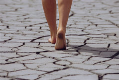 Woman walking barefoot across cracked earth.  Stock Photos
