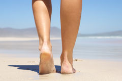 Woman walking barefoot on beach from behind Stock Image