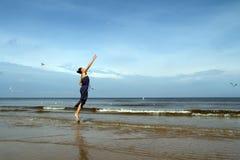 Woman walking barefoot on the beach jumping and feeding white gu. Baltic sea,   woman  walking along the beach  jumping and feeding  white gulls Royalty Free Stock Image