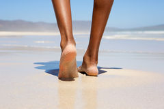 Woman walking barefoot on beach Royalty Free Stock Photo