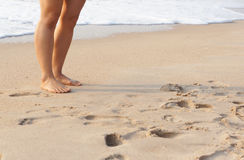 Woman walking. Barefoot on sunny beach in summer day Royalty Free Stock Photo