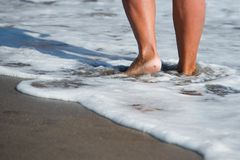 Woman walking barefoot on sunny beach Royalty Free Stock Images