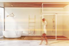 Woman walking in bathroom with shower. Woman walking in spacious bathroom interior with white walls, tiled floor, comfortable bathtub and shower stall with glass stock photography
