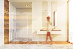 Woman walking in bathroom with shower. Young woman walking in modern bathroom with white and wooden walls, shower with glass door and double sink. Toned image stock photo