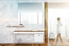 Woman walking in bathroom with sink. Unrecognizable woman walking in large bathroom with white and wooden walls and white sink on wooden countertop. Big mirror stock photography