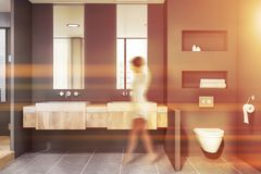 Woman walking in bathroom with toilet stock photo