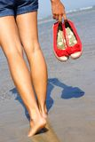 Woman walking on beach. Woman walking on the beach holding her shoes stock photos